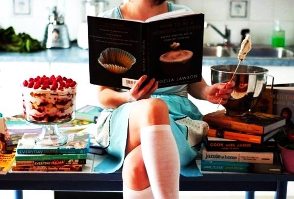 девушка читает кулинарную книгу на столе