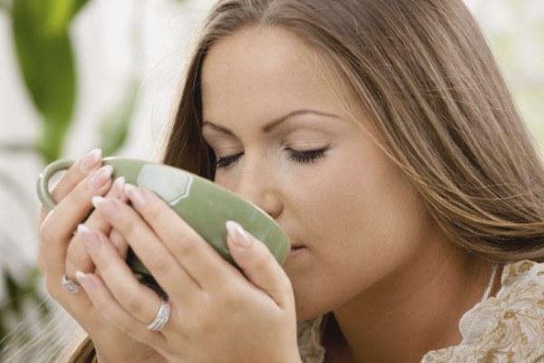 девушка пьет жидкость с чашки
